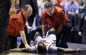 Trainers check on Louisville guard Kevin Ware after he broke his lower right leg during the first half of the Midwest Regional final against Duke in the NCAA college basketball tournament.