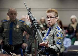 A Firearms Training Unit detective of the Connecticut State Police holds up a Bushmaster AR-15 rifle, the same make and model of gun used by Adam Lanza in the Sandy Hook School shooting.