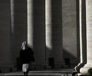 A nun walks under the Bernini colonnade in St. Peter's Square at the Vatican, Friday, Feb. 15, 2013.