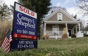 In this Tuesday, March 12, 2013, photo, a sold sign is posted in front of a home for sale in Mariemont, Ohio.