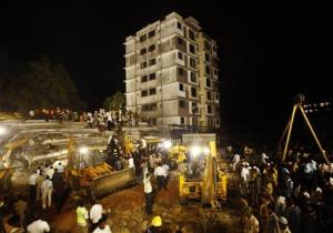 Rescue workers search for trapped people after a building collapsed in Thane, Mumbai, India, Thursday, April 4, 2013.