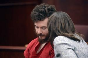 A defense attorney talks to James Holmes during his arraignment in Centennial, Colo., March 12, 2013.