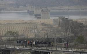 Tourists look over the north side of the Bridge of Freedom which was destroyed during the Korean War, north of Seoul, South Korea, Friday, April 5, 2013.