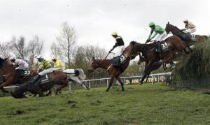 In this photo from last year's Grand National, Synchronized, left,  falls after a jump. The horse was later euthanized.