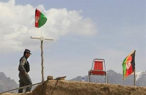 An Afghan policeman stands guard on the roof of a house in the outskirts of Kabul Saturday.
