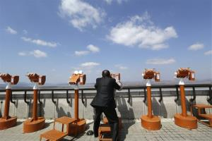 A South Korean man uses binoculars to watch North Korean territory at the unification observation post near the border village of Panmunjom, that has separated the two Koreas since the Korean War, in Paju, north of Seoul, South Korea, Sunday, April 7, 2013. South Korea said its top military officer...