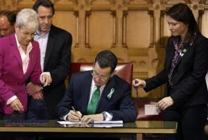 In this April 4, 2013, photo, Connecticut Gov. Dannel Malloy signs legislation that includes new restrictions on weapons and large capacity magazines, a response to the Newtown shooting.
