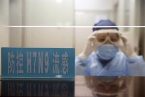 A health worker wearing protective clothing adjusts her goggles at a desk with a sign that reads Prevention of H7N9 Flu at a hospital in Shanghai.