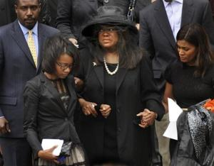 Chaz Ebert, center, wife of film critic Roger Ebert leaves Holy Name Cathedral after his funeral in Chicago, April 8, 2013.