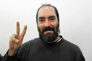 In this 2009 file photo, Ultra-Orthodox West Bank settler Jack Tytell flashes the victory sign inside a court in Petah Tikva, Israel.