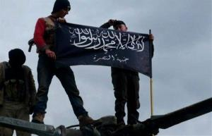 Rebels from al-Qaida affiliated Jabhat al-Nusra waving their brigade flag on the top of a Syrian air force helicopter.
