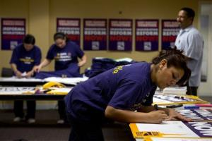 Denise Villagomez, a union member, writes on a sign as she and other union volunteers prepare for Wednesday's immigration reform rally at the Service Employees International Union (SEIU) in Washington.