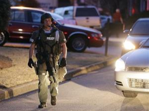 A police officer leaves the scene after an explosion and gunshots were heard Wednesday, April 10, 2013 in Suwanee, Ga.