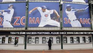 A person stands in front of ticket windows at Wrigley Field, Wednesday, April 10, 2013, in Chicago.