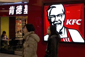 Chinese women walk past a customer eating inside a KFC restaurant at a shopping mall in Beijing Monday, Feb. 25, 2013.