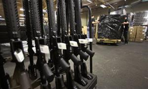 A rack of AR-15 rifles stand to be individually packaged as workers move a pallet of rifles for shipment at the Stag Arms company in New Britain, Conn., Wednesday.