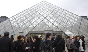 Visitors stands in front of to entrance in Louvre museum Paris, France, Wednesday, April 10, 2013.