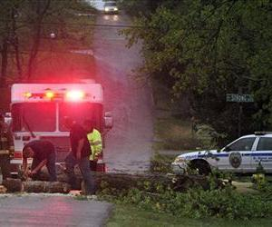 Huntsville Fire and Rescue crews remove a downed tree blocking traffic on Dell Avenue as strong storms passed through Huntsville, Ala., April 11, 2013.