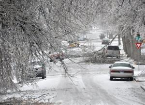 Icy branches partially block a city street and fall amid parked cars, Wednesday, April 10, 2013, in Sioux Falls, SD.
