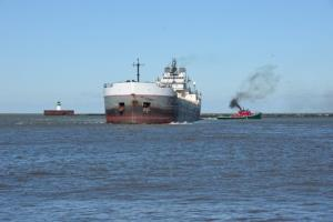 A tug boat guides a ship on Lake Erie.