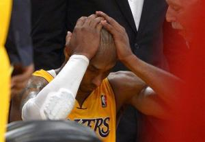Kobe Bryant puts his head in his hands after being injured during the second half of their game against the Golden State Warriors, Friday, April 12, 2013, in Los Angeles.