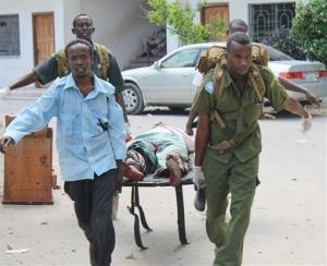 Somali soldiers carry a wounded civilian from Mogadishu's court complex after a siege by militants, Sunday, April 14, 2013. Warning: The following pictures contain images of dead civilians.