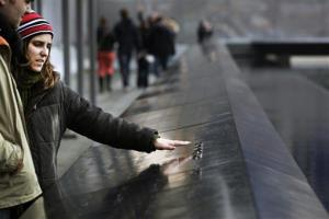 A visitor reaches out to touch names engraved in memory during a visit to the National September 11 Memorial and Museum, Monday, Feb. 25, 2013 in New York.