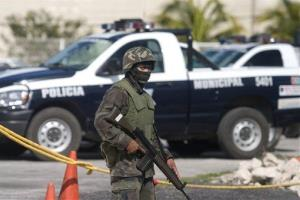 A soldier guards police vehicles outside a police station in Cancun, Mexico.