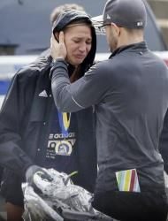 An unidentified Boston Marathon runner is comforted as she cries in the aftermath of the explosions.