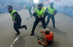 Police officers react to a second explosion at the finish line of the Boston Marathon in Boston, Monday, April 15, 2013.