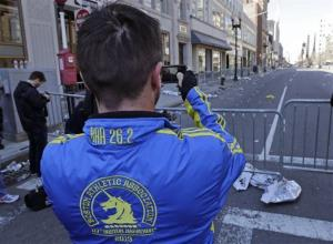 Paul McRae, a native of New Zealand now living in Jacksonville, takes a photograph of an empty Boylston Avenue near the Boston Marathon finish line, in Boston, Tuesday, April 16, 2013.