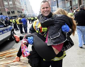 In this Monday, April 15, 2013 photo, Boston Firefighter James Plourde carries an injured girl away from the scene after a bombing near the finish line of the Boston Marathon in Boston.