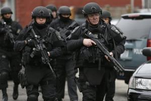 Police in tactical gear conduct a search for a suspect in the Boston Marathon bombings Friday in Watertown, Mass.
