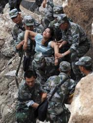 Rescuers save an injured woman in Baosheng Township, Sichuan province.