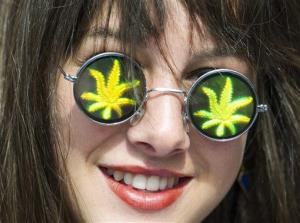 A women wears glasses with the likeness of marijuana leaves during the annual marijuana 420 smoke off at Dundas Square in Toronto on Friday, April 20, 2012.