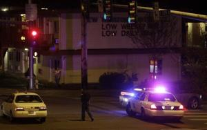 A Washington State Patrol trooper directs a driver away from a street near the scene of an overnight shooting at an apartment complex in Federal Way, Wash.