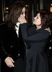 Sharon Osbourne clasps a hand over husband and British musician Ozzy Osbourne's mouth as they arrive for the Classic Rock awards in central London, Monday, Nov. 3, 2008.