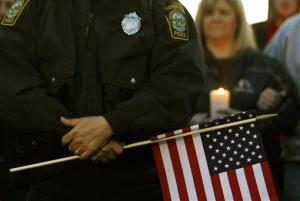 Watertown Police officer Brandon O'Neill holds a flag during a vigil for the victims of the Boston Marathon bombing, Saturday, April 20, 2013, in Watertown, Mass.