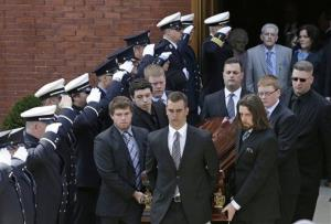 An honor guard from area Fire Departments salutes as pallbearers carry the casket of Boston Marathon bomb victim Krystle Campbell, 29, out of St. Joseph's Church after her funeral in Medford, Mass.