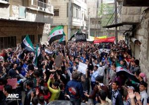 This citizen journalism image shows anti-Syrian regime protesters chanting slogans and waving the Syrian revolutionary flag during a demonstration, in Aleppo, Friday, April 19, 2013.