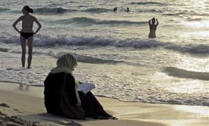 In this Thursday, Sept. 6, 2012, file photo, a woman reads the Quran on a beach as people in bikinis sunbathe and swim at sunset in Dubai, United Arab Emirates.