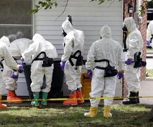 Federal agents wearing hazardous material suits inspect a trash can outside the house of Paul Kevin Curtis in Corinth, Miss.,  April 19, 2013.