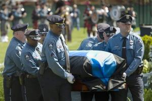 In a photo provided by Massachusetts Institute of Technology, MIT police pallbearers carry the casket of fallen MIT officer Sean Collier.