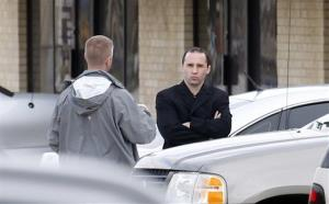 Everett Dutschke, right, confers with a federal agent near the site of a martial arts studio he once operated, Wednesday, April 24, 2013 in Tupelo, Miss.