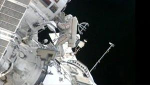 In this still image made from video provided by NASA, a Russian cosmonaut installs shields to protect against zooming pieces of junk to improve the safety of his orbiting home Monday, Aug. 20, 2012.