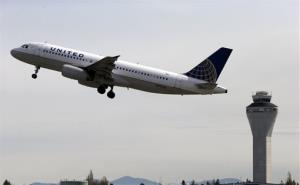 In this April 23 photo, a United Airlines jet departs in view of the air traffic control tower at Seattle-Tacoma International Airport.