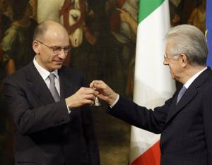 Premier Enrico Letta, left, takes the cabinet minister bell handed over by former Premier Mario Monti during a handover ceremony in Rome, Sunday, April 28, 2013.