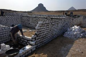 In this Sunday, Jan. 13, 2013 photo, Egyptian laborers work at the new construction site of the illegal expansion of a local cemetery that is seen spreading toward Egypt's first pyramids and temples.