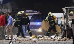 Policemen and firefighters inspect the scene of an explosion in downtown Prague today.