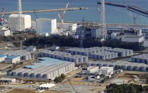 Cylindrical tanks built for storage of polluted water are seen near the four reactor buildings, background, at the tsunami-crippled Fukushima Dai-Ichi nuclear plant in Okuma, northern Japan.